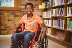 38133514 - portrait of little boy sitting in wheelchair at the library